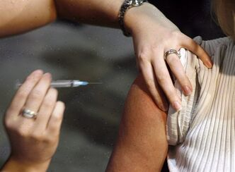 A patient gets a shot during a flu vaccine program in Calgary on Oct. 26, 2009. . THE CANADIAN PRESS/Jeff McIntosh