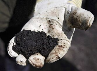 An oil worker holds raw oilsands near Fort McMurray, Alta., on July 9, 2008. THE CANADIAN PRESS/Jeff McIntosh