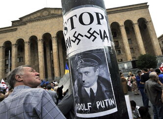 A poster depicts Russian Prime Minister Vladimir Putin as Nazi leader Adolf Hitler in front of Georgia's Parliament building.