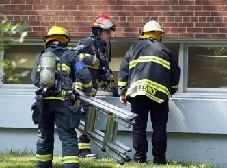 Firefighters move equipment through a basement window as they work on a fire in the cafeteria area of Kelvin High School.