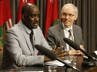 Minister of Infrastructure and Transportation Steve Ashton, right, introduces Fisaha Unduche to the media today.