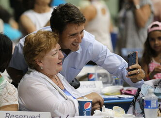 Justin Trudeau takes a selfie with Norma Padilla at the Israel pavilion.