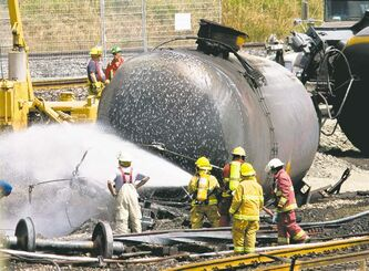 Firefighters spray foam on the train crash site in Lac-Mégantic, Que., Sunday, eight days after the horrific train derailment.