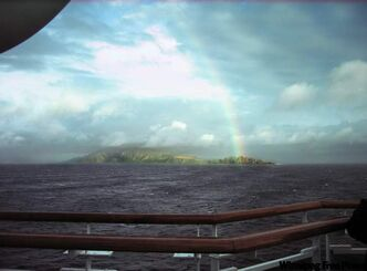 Rare sighting of a rainbow piercing the gloom and touching Cape Horn.