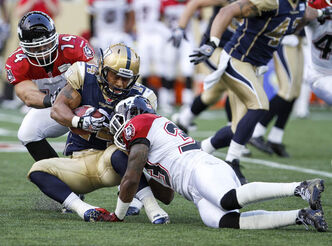 Aaron Woods is brought down by Stampeders' Chris Randle, 33, and Matt Walter, 14 Friday night at Investors Group Field. The Blue Bombers lost 37-24.