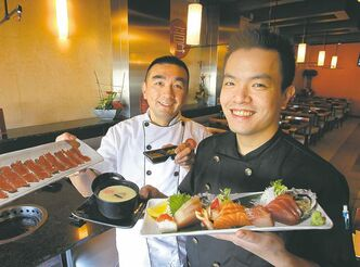 Dee Chan, left, and David Kong with chawan mushi (in bowl) and platter of sashimi  (including albacore, big eye tuna, and yellowtail).