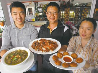 The Ung family holds up Thai Bochi specialties; from left, Charles with sour beef soup, Chhay with marinated grilled chicken (both Cambodian dishes) and  Kanyarat with Thai fish cakes.