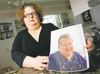Dana Brenan holds a photo of her mother, Heather Brenan, who died after being sent home from hospital.