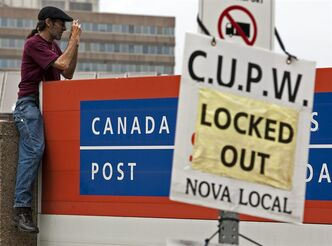 An unidentified man takes pictures as locked out Canada Post employees march outside the main postal facility in Halifax on June 18, 2011. THE CANADIAN PRESS/Andrew Vaughan