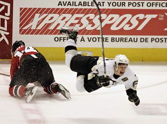 Pittsburgh Penguin Sidney Crosby winces as he flies through the air after being hit by Ottawa Senators Andrej Meszaros (14) in 2006. Player safety is a growing concern for the NHL.