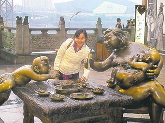 Yanjiao (Ivy) Zhang at a statue celebrating 'Hot Pot' in Chongqing.