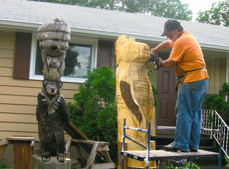 Wood carver Bruce Macdonald at work in his front yard on one of his pieces.
