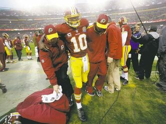 Redskins quarterback Robert Griffin III is helped off the field after banging up a knee on Sunday.