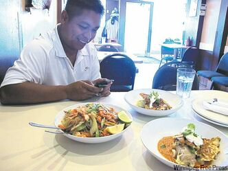 Ron Cantiveros (left) and chef Harry Mogatas from the Rice Bowl teamed up to create Philippine-inspired  Winnipeg dishes such as pancit with kubasa and smoked goldeye (below), cabbage rolls with rice and calderata (right two dishes in left photo).