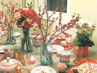 This charming tablescape features vintage preserve jars filled with crimson red Ilex berries and a simple arrangement of red and blush-coloured carnations set among mix and match dishes.