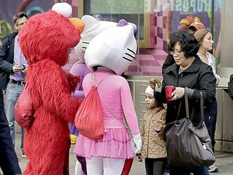 A woman opens her wallet as Hello Kittys and an Elmo surround her.