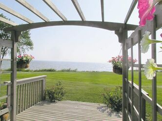 The view of Victoria Beach is framed by a wooden pergola.