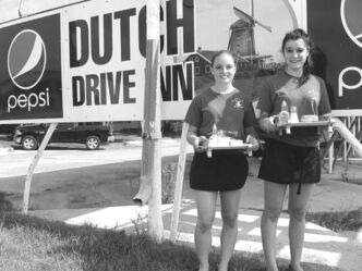Carhops Erika Scott (left) and Chloe Watts in front of the landmark Dutch Drive In in The Pas.