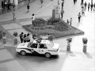 A police car is parked at the entrance to the Chunxi Road pedestrian mall in Chengdu.
