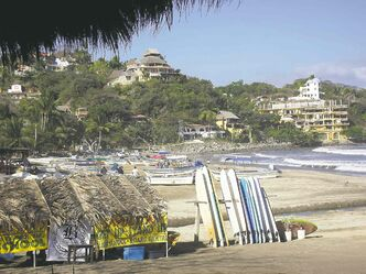 A beach scene in Sayulita, with surf boards ready to enter the waves.