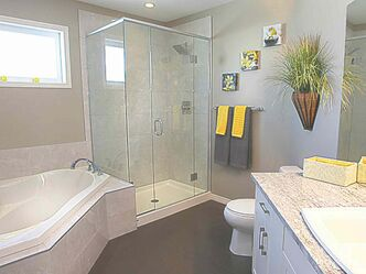 The spacious ensuite features a corner soaker tub with light-taupe porcelain tile surround beneath an oversize transom window next to a five-foot tile shower with frameless tempered-glass surround.
