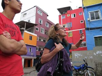 A guide notes newly painted houses as she leads a group of middle-class Brazilians on a tour of Rocinha, a favela in Rio de Janeiro that is home to about 250,000 people.