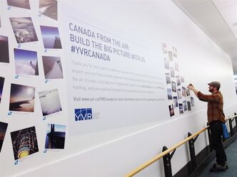 A person attaches a photo to an Air Canada photo installation in the domestic terminal at the Vancouver International Airport in Vancouver in this undated handout photo. If your snapshot from the window seat makes Canada look good, the Vancouver Airport Authority wants to see it. The organization has launched an online gallery that celebrates the beauty of the country as seen from above. THE CANADIAN PRESS/HO - Air Canada