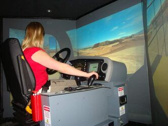 "A student learns to ""drive"" a large truck across a simulated landscape."