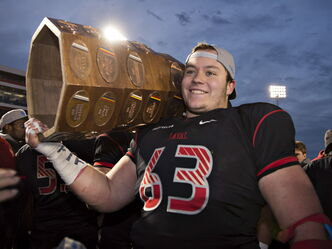 Laval's Pierre Lavertu raises the Dunsmore Cup last fall. The Rouge et Or offensive lineman is expected to be either a Redblack or a Bomber.