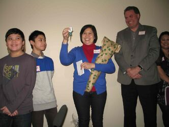 Merlinda, with her sons (left to right) Jann and James, displays the keys to her new Habitat for Humanity home. Also pictured, at far right, is Larry Wandowich, chief community relations and marketing officer for Manitoba Liquor & Lotteries.