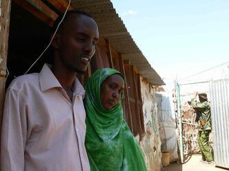 Farah and Hassan Mohamed Abdi, outside their home in Dagahaley refugee camp, Dadaab, while Kenyan security forces hired by the Free Press to prevent a reporter's kidnapping guard the entrance to their home.
