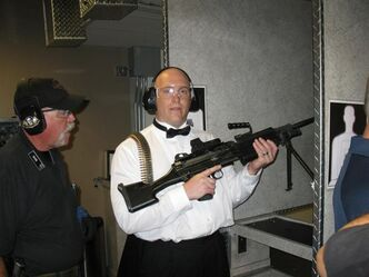 This July 28, 2012 photo provided by Bob MacDuff shows MacDuff holding an automatic weapon at the Gun store in Las Vegas after his