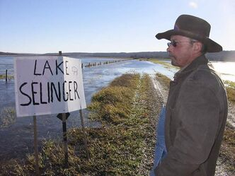 Gene Nerbas in front of fields flooded by the Shellmouth Dam in 2011, where someone had placed a Lake Selinger sign.