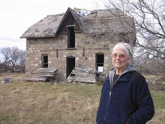 Bernice Still in front of one of over 400 abandoned heritage homes she has documented.