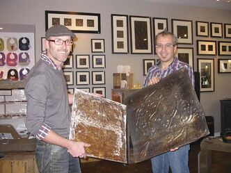 Tyler Kilkenny (left) and Todd Sawyer display tin salvaged from abandoned buildings.