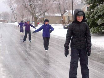 Kids skate on an ice-covered street in Kingston, Ont., on Saturday.