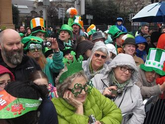 Spectators watch the St. Patrick's Day parade in Dublin, Sunday, March 17, 2013. Never mind the fickle Irish weather - a chilly, damp Dublin celebrated St. Patrick's Day with artistic flair Sunday as the focal point for a weekend of Irish celebrations worldwide. (AP Photo/Shawn Pogatchnik)