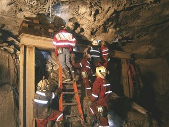 In this photo taken and released by PT Freeport Indonesia, Friday, May 17, 2013, the Indonesian unit of Arizona-based Freeport-McMoRan Copper & Gold Inc, rescuers gather inside a tunnel that collapsed on Tuesday morning as they continue their attempt to rescue trapped workers at Big Gossan mining area in Mimika, Papua province, Indonesia. Mining activities at a giant U.S.-owned gold and copper mine in Indonesia are halted for four consecutive days as rescuers manually dig through a caved-in mine tunnel looking for about 23 trapped workers, the mine operator said. (AP Photo/PT Freeport Indonesia) NO ARCHIVE, NO SALES -----