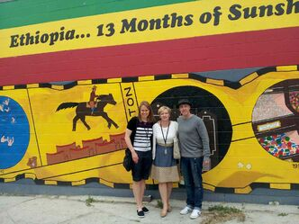 Klassen, Cardwell-Hoeppner, and Burpee stand in front of a mural painted on the side of Gohe Ethiopian Restaurant (533 Sargent Ave.).