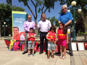 Young models help Carl Shier (from right), Jim Rondeau and Shawn Feel announce the expanded loaner life jacket program.