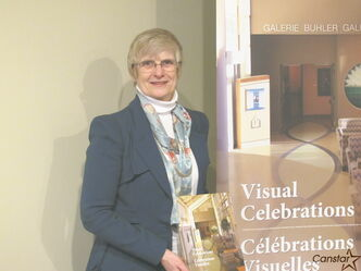 Pat Bovey holds a copy of the book Visual Celebrations which documents the Buhler Gallery's first five years.