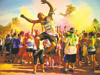 Runners at one of last year's Color Me Rad 5km road race celebrate the colourful experience.