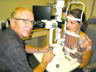 Don Porter demonstrates an eye examination on his colleague, Kim Elcheshen.