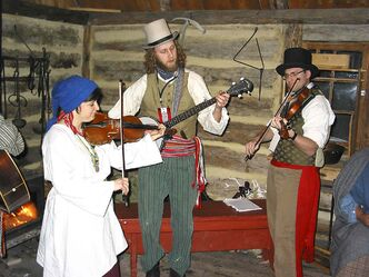 From left to right: Sabine Trégouët, Ian McAmmond and Stephen Challes entertain visitors this past February at Festival du Voyageur in a cabin that would have been used by voyageurs when the river was frozen during the winter. The cabin is located at Fort Gibraltar, which will undergo rehabilitation and restoration work in light of $100,000 of provincial funding under the Winnipeg Community Infrastructure Program.