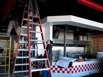 Workers work on the ceiling at the soon-to-be-opened Five Guys on Portage Ave.