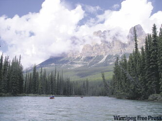 Canoeists enjoy a paddle down the Bow River past Castle Mountain in Banff National Park.