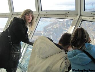 Only the brave of heart dare to look out the windows of the CN Tower Skypod. Megan Kirbyson looks back at the author, who is glued to the wall.