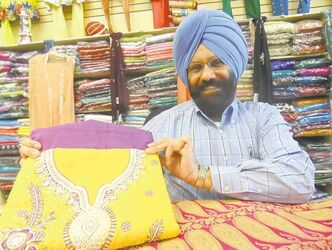 Parminder Singh Buttar shows off some of the bright fabrics available for saris and suits.