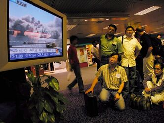 FILE - In this Tuesday, Sept. 11, 2001 file picture, travellers at Singapore's Changi International Airport stop to watch live pictures of smoke billowing over lower Manhattan after a terrorist attack on the World Trade Center in New York. From all parts of the world, even in New York itself, most people experienced the events of Sept. 11, 2001 on television. (AP Photo/Charles Dharapak)
