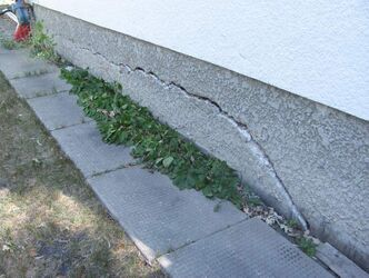Large cracks in above-grade basement were caused by sinking and shifting.